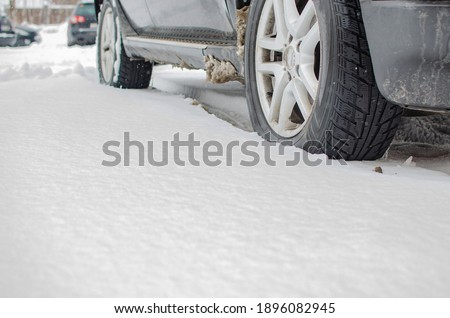 Closeup of the car tire on winter road covered with snow. Snowflakes are on the rubber wheel. Royalty-Free Stock Photo #1896082945