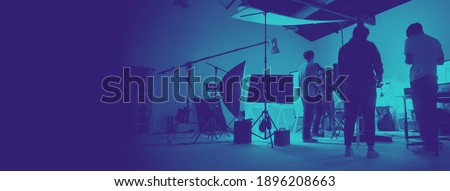 Two tone images of behind the scene of photo shooting production set up in the big studio. Professional crew team working and camera equipment in silhouette. And copy space added. Royalty-Free Stock Photo #1896208663