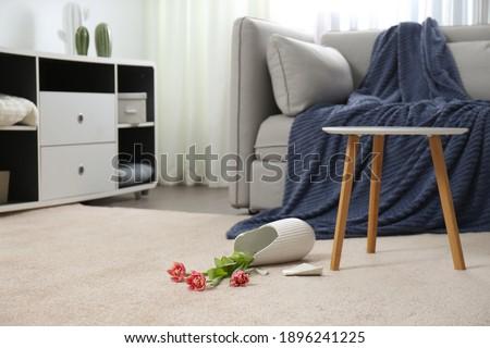 Broken ceramic vase on floor in room Royalty-Free Stock Photo #1896241225
