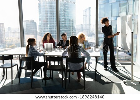 Young African American female coach or speaker make flip chart presentation to diverse businesspeople at meeting in office. Woman tutor or trainer present project on whiteboard to diverse colleagues. Royalty-Free Stock Photo #1896248140