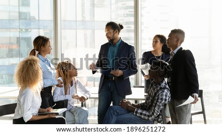 Diverse multiethnic businesspeople gather at casual meeting in office, brainstorm over business project together. Multiracial colleagues talk discuss company financial paperwork. Teamwork concept. Royalty-Free Stock Photo #1896251272
