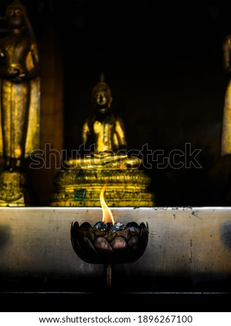 Light a candle to pay homage to the Buddha image for the birthday.
