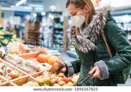 Woman wearing ffp2 face mask shopping groceries in supermarket