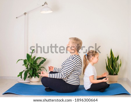 Senior woman and child meditating at home. Old granny with her granddaughter sitting in yoga position back to back on fitness mat.