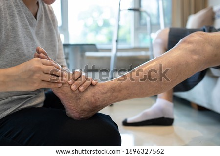 Foot massage physical therapy to relieve muscle spasms,massage the tired muscles of senior woman,feet numb from diabetes,old elderly with diabetic numbness of the toes,problems of peripheral nerves