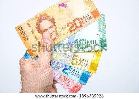Costa Rican money, Colones, All banknotes fanned out and held in a male hand, White background Royalty-Free Stock Photo #1896335926