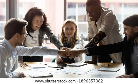 Happy motivated young and older generation multiracial business people joining fists, showing support and team spirit together, celebrating corporate achievement or success at meeting in office. Royalty-Free Stock Photo #1896357082