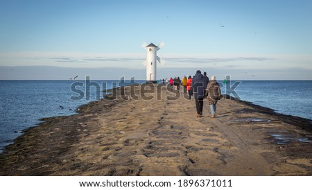 People walking towards the lighthouse in Swinoujscie in Poland, Winter Royalty-Free Stock Photo #1896371011