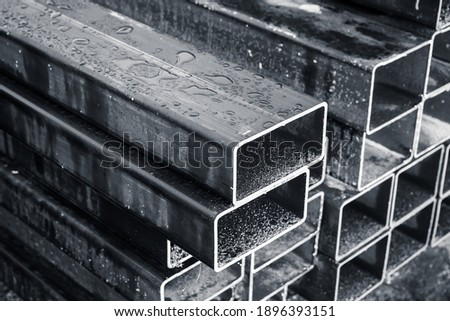 Stacked steel pipes with rectangular cross-section, close-up monochrome photo with selective focus Royalty-Free Stock Photo #1896393151