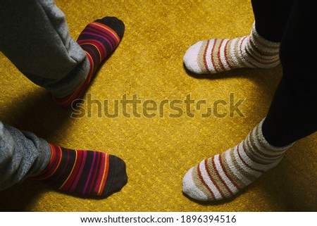 feet of woman and man with colorful socks on yellow carpet. love in the house #1896394516