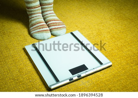 woman feet with socks and scales on yellow carpet #1896394528