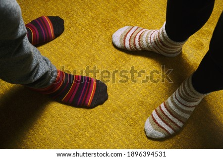 feet of woman and man with colorful socks on yellow carpet. love in the house #1896394531