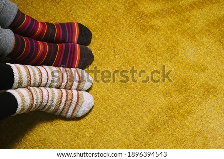 feet of woman and man with colorful socks on yellow carpet. love in the house #1896394543