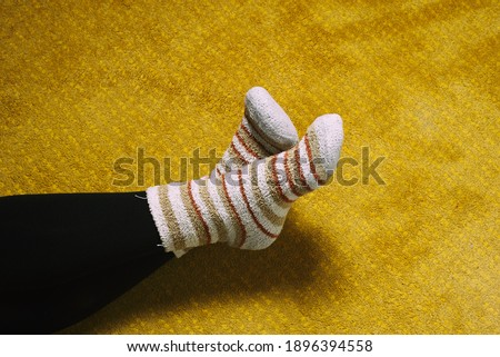 woman feet with crossed colorful socks on yellow carpet. waiting #1896394558