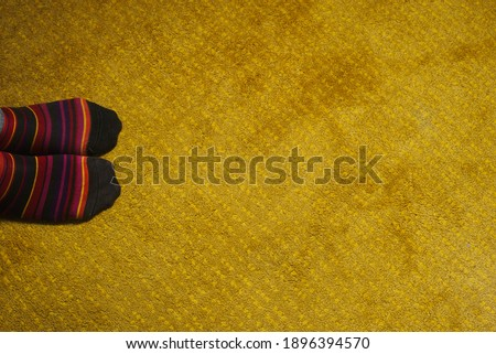 feet of man with colorful socks on yellow carpet #1896394570