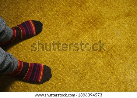 feet of man with colorful socks on yellow carpet #1896394573