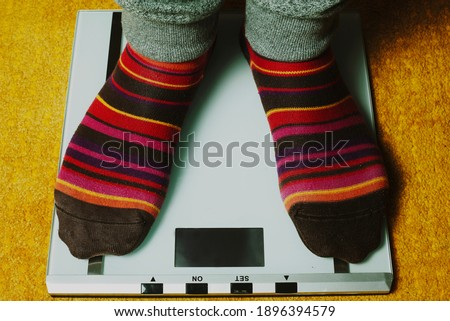 man feet with colorful socks step on the weight scale #1896394579