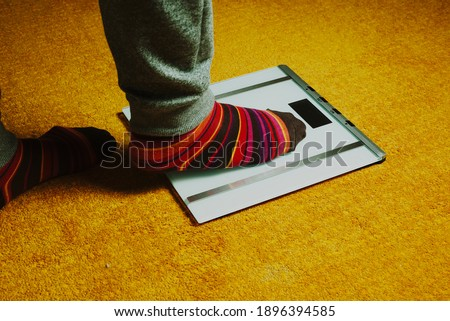 man feet with colorful socks step on the weight scale #1896394585