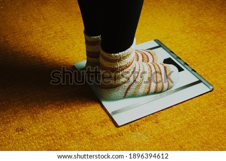 woman feet with socks and scales on yellow carpet #1896394612