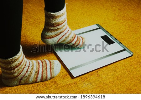 woman feet with socks and scales on yellow carpet #1896394618