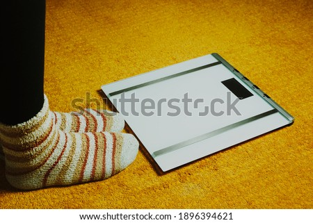 woman feet with socks and scales on yellow carpet #1896394621