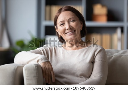 Head shot portrait positive mature woman with healthy smile sitting on cozy couch, happy middle aged female looking at camera, posing for photo at home, enjoying leisure time, relaxing on sofa alone