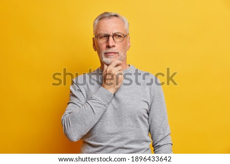 Senior thougthful man holds chin and looks pensively aside makes plannings wears spectacles and casual grey jumper isolated over vivid yellow background. Handsome grandfather considers something Royalty-Free Stock Photo #1896433642