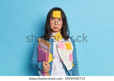 Unhappy tired Asian student concentrated above has sad expression wears spectacles for vision correction holds folders papers stuck with paper clips isolated over blue background learns formulas Royalty-Free Stock Photo #1896446713