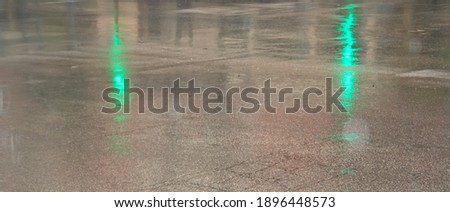 Rain-soaked asphalt with multicolored glare from car headlights and traffic lights. #1896448573