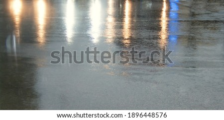 Rain-soaked asphalt with multicolored glare from car headlights and traffic lights. #1896448576