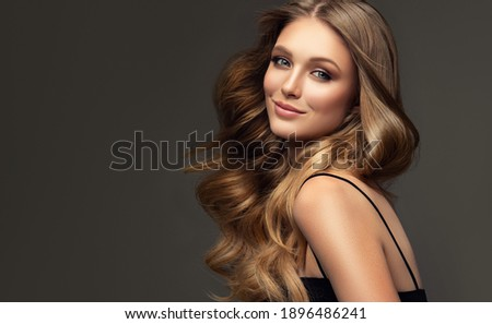 Beauty blonde girl with long  and   shiny wavy  hair .  Beautiful   woman model with curly hairstyle . Fashion, cosmetics and makeup Royalty-Free Stock Photo #1896486241