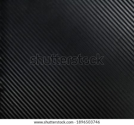 A dark carbon fiber material shot. A dark industrial texture suitable as a background on compositions