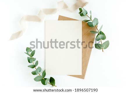 Mockup invitation, blank greeting card and green leaves eucalyptus. Flat lay, top view. Royalty-Free Stock Photo #1896507190