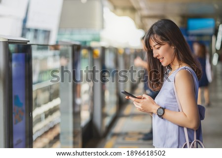 Young Asian woman passenger using social network via smart mobile phone in subway train when traveling in big city,japanese,chinese,Korean lifestyle and daily life, commuter and transportation concept Royalty-Free Stock Photo #1896618502