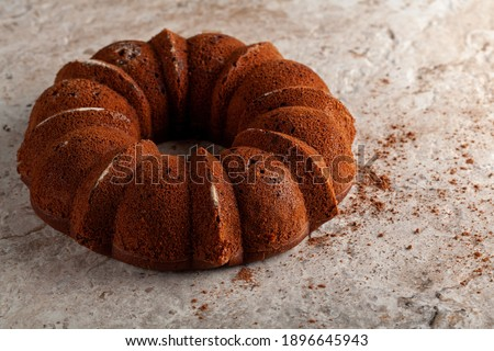 A round sponge cake fresh out of oven with crumbles and cacao powders cooling on top of a marble or stone kitchen countertop. The impression of the cake mold is seen on the rugged appearance of it. Royalty-Free Stock Photo #1896645943