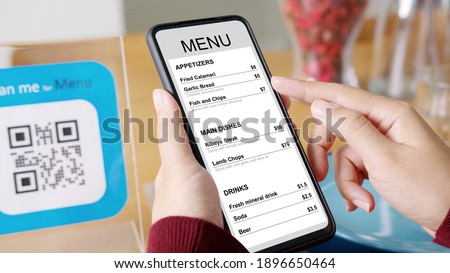 Hand's customer scan QR code for online menu service at table in restaurant during pandemic coronavirus. New normal contactless technology lifestyle protection coronavirus pandemic in restaurant Royalty-Free Stock Photo #1896650464