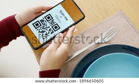 Hand's customer scan QR code for online menu service at table in restaurant during pandemic coronavirus. New normal contactless technology lifestyle protection coronavirus pandemic in restaurant Royalty-Free Stock Photo #1896650605