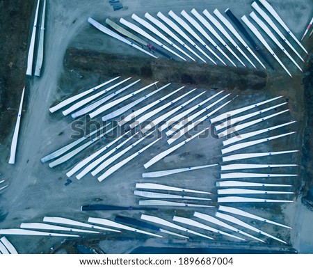 Blades for wind turbines stored outside of a factory waiting for shipping. Royalty-Free Stock Photo #1896687004