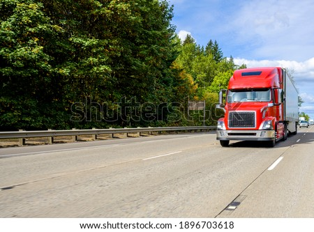 Red big rig industrial grade bonnet long hauler diesel semi truck with high roof cab and refrigerator semi trailer running with commercial cargo on the wide highway road with green trees hillside Royalty-Free Stock Photo #1896703618