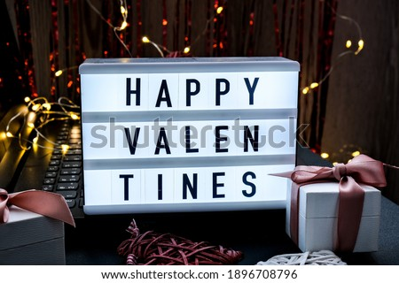 Lightbox with text HAPPY VALENTINES gift boxes on light bokeh background. Saint Valentines Day. Holidays background and textures.