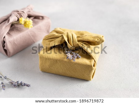 reusable sustainable gift wrapping in linen fabric. Furoshiki gifts. zero waste concept. close-up. selective focus Royalty-Free Stock Photo #1896719872