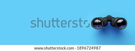 Binoculars on a light blue background. Banner. Flat lay, top view. Royalty-Free Stock Photo #1896724987