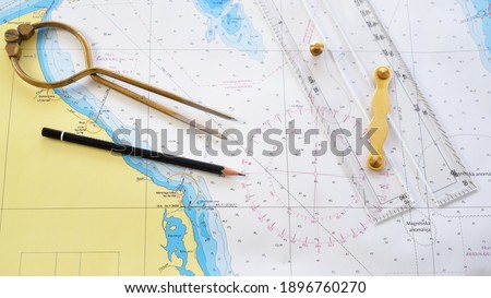 """Antique W HC 6"""" brass dividers calipers nautical navigation chart tool, pencil, parallel ruler, old white chart close-up. Vintage still life. Sailing, travel accessories. Planning, concept art Royalty-Free Stock Photo #1896760270"""
