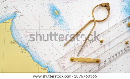 """Antique golden vintage W HC 6"""" brass dividers calipers nautical navigation chart tool, parallel ruler, old white chart close-up. Vintage still life. Sailing, travel accessories Royalty-Free Stock Photo #1896760366"""