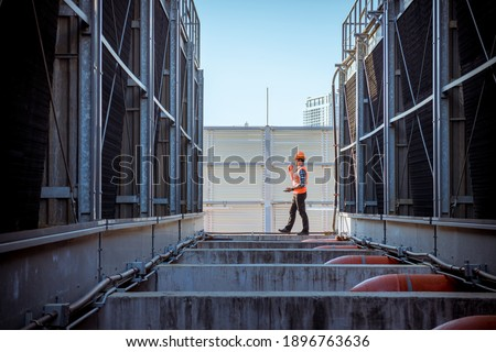 Engineer under checking the industry cooling tower air conditioner is water condenser cooling tower air chiller HVAC of large industrial building to control air system. Royalty-Free Stock Photo #1896763636