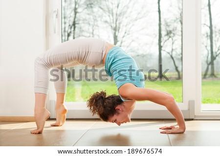 Young woman practicing yoga - Urdhva Dhanurasana / Upward bow pose indoor in fron of the window #189676574