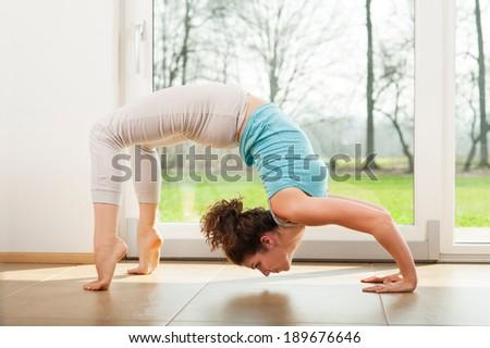 Young woman practicing yoga - Urdhva Dhanurasana / Upward bow pose indoor in fron of the window #189676646