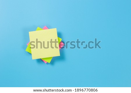 Stack empty sticky post note paper sheet on blue background. Royalty-Free Stock Photo #1896770806