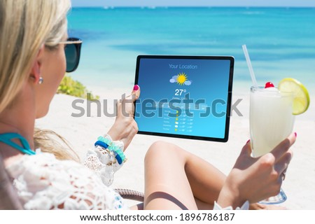 Woman viewing weather forecast on tablet while relaxing on the beach Royalty-Free Stock Photo #1896786187