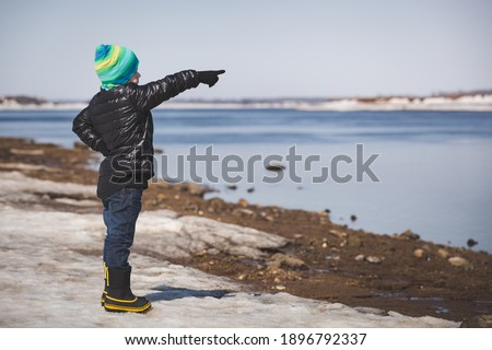 A little boy in warm clothes stands on the shore. The child rejoices at the beginning of spring. The kid raised his hand and points to something in the distance. Spring, joyful mood. Walks in the park Royalty-Free Stock Photo #1896792337